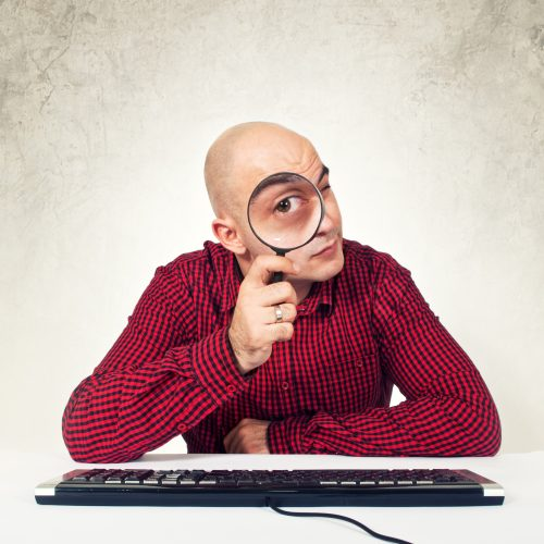 Man with magnifying glass sitting in fron to computer keayboard