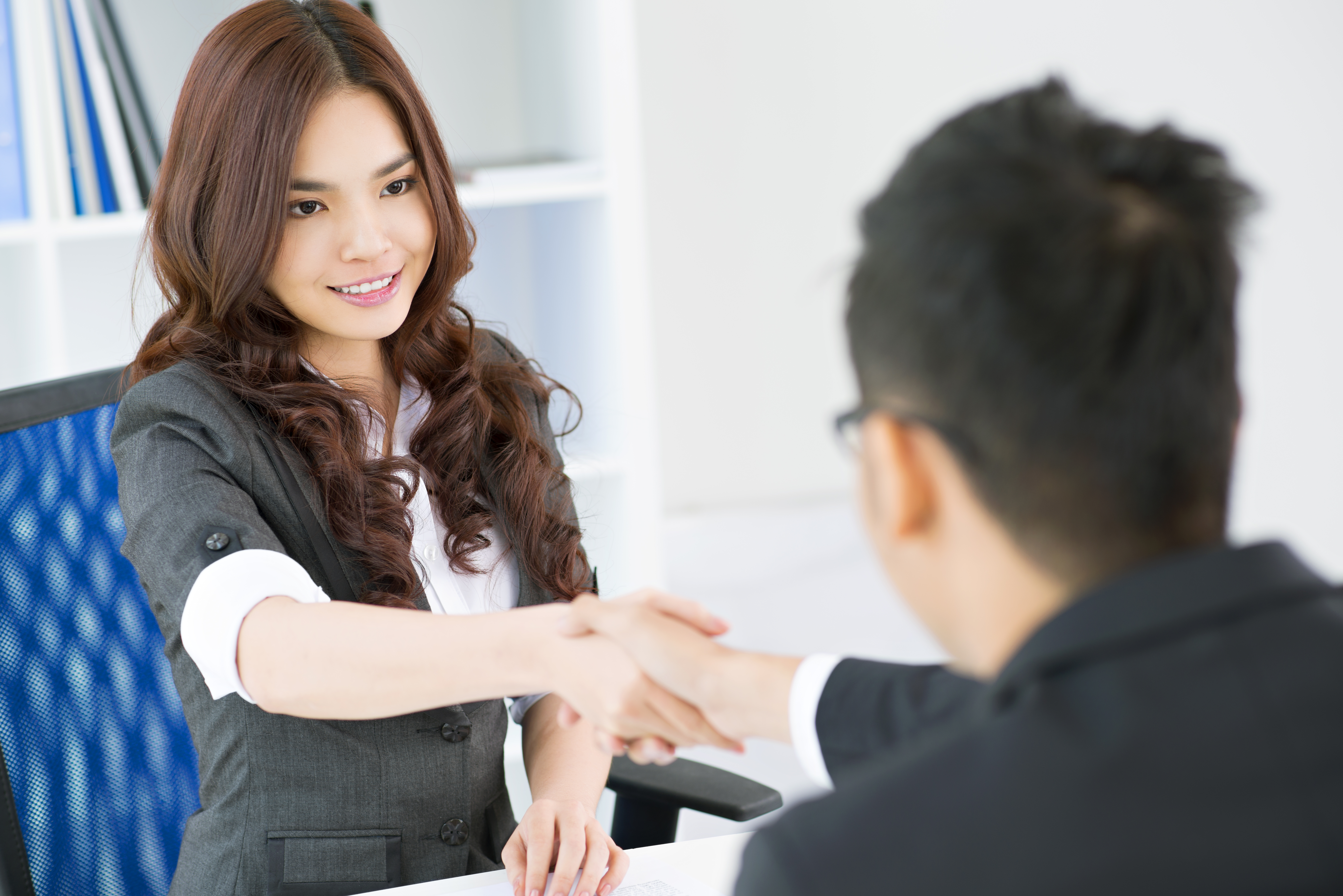 Image of a business woman shaking hands with a man - Respect your town planner he is a great asset to help you obtain development approval