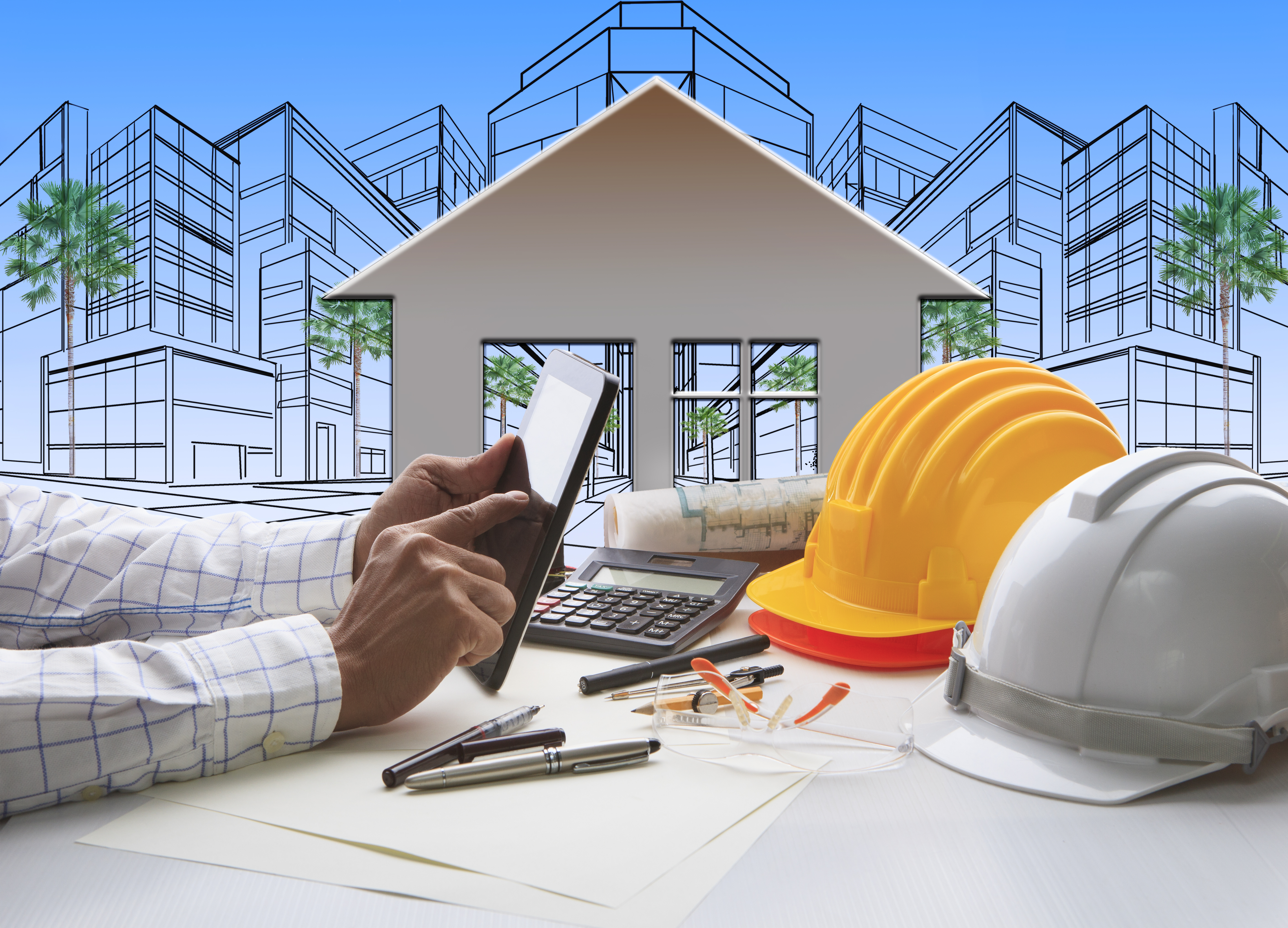 Image of a property investor using a tablet and over a table with builder helmets and blue prints - represents that Another great Property Development Tip is to be sure to find quality builders